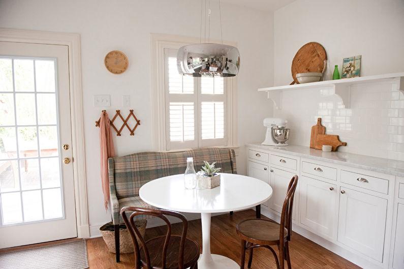 Белая кухня с небольшим диванчиком
