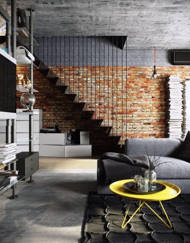 Кирпичная стена на фоне высокого бетонного потолка выглядит строго и основательно