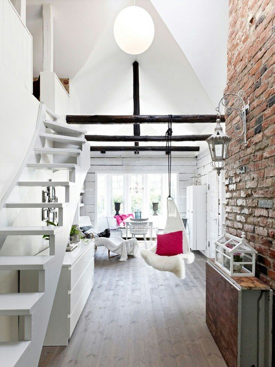 Белая мебель, высокие потолки и кирпичная стена создают по настоящему уютную атмосферу