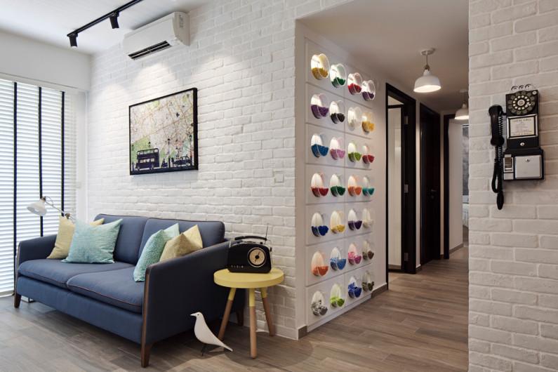 Синий диван и интересные элементы декора на фоне белой кирпичной стены