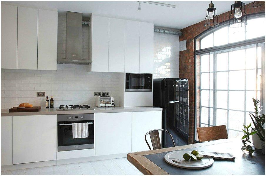 Белая кухня с акцентами в виде чёрного цвета и кирпичной кладки
