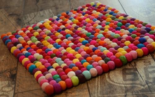 Яркий цветной коврик из помпонов пряжи