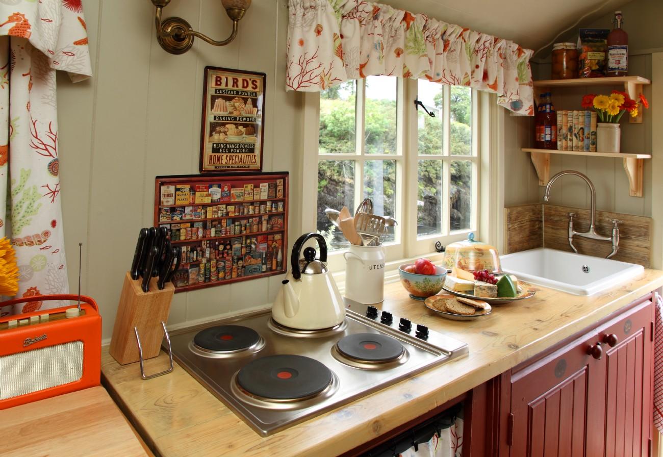 Открытые деревянные полочки над раковиной в интерьере маленькой кухни