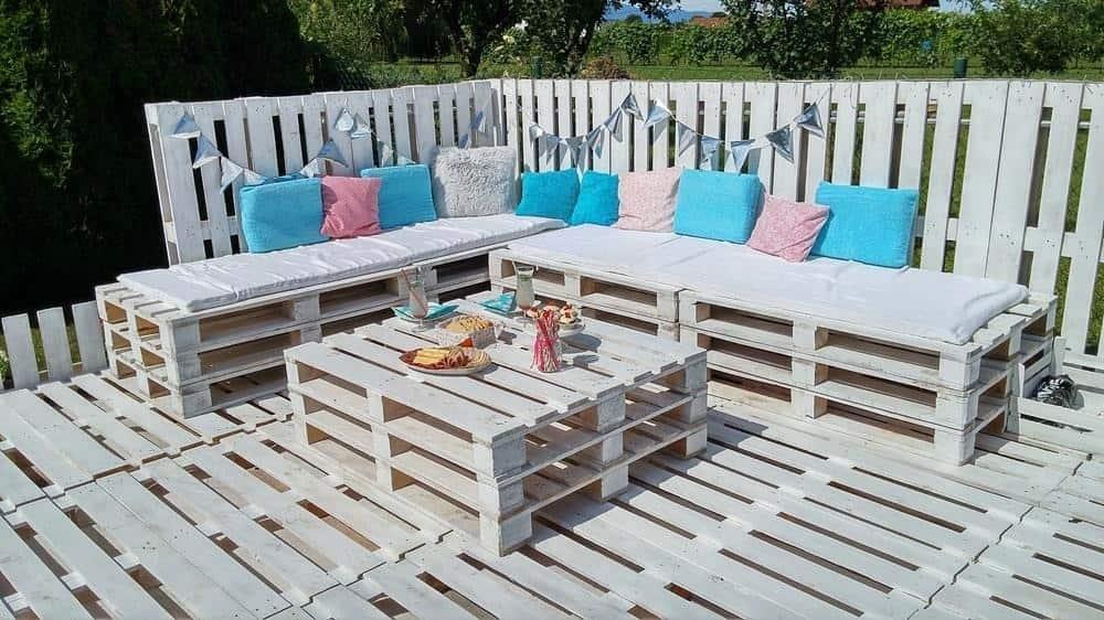 Терраса из выбеленных деревянных поддонов в сочетании с цветными подушками смотрится легко и непринужденно