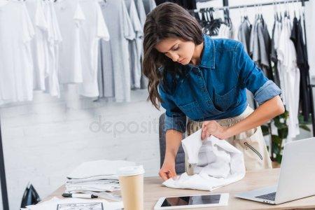 Female Fashion Designer Folding Shirt Table Coffee Digital Devices Clothing — стоковое фото