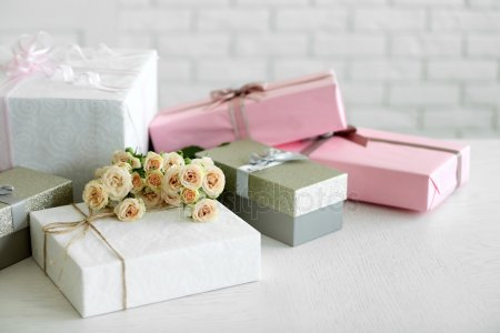 Декорированой подарочной коробки и букет роз на фоне белого кирпича стены — стоковое фото