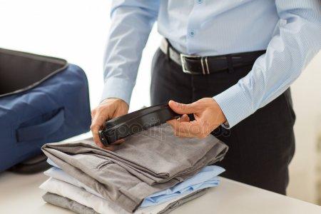 Бизнесмен, упаковывающий одежду в несессер — стоковое фото