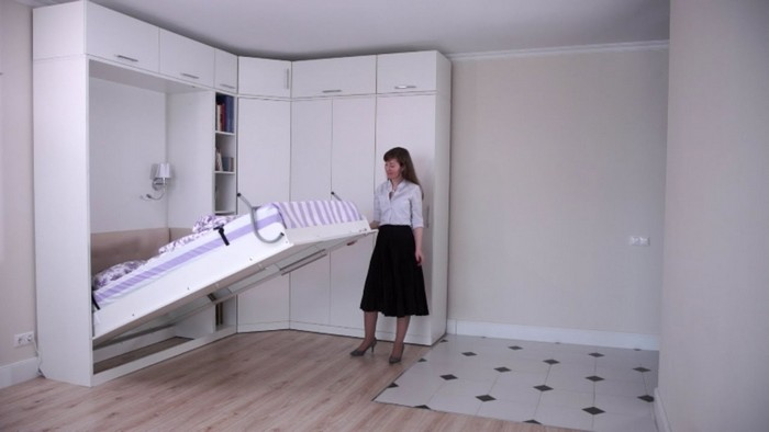 Женщина раскладывает кровать-трансформер