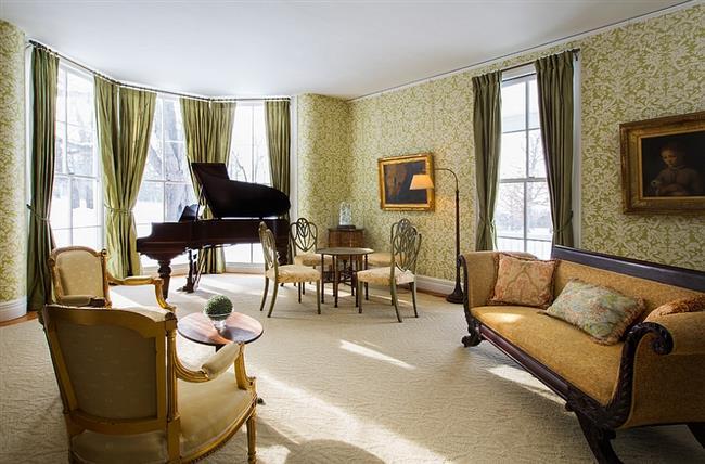 Узорчатые зеленые обои и зеленые портьеры в стильной гостиной.