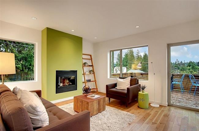 Стильная гостиная светлых тонов с зеленой стеной.