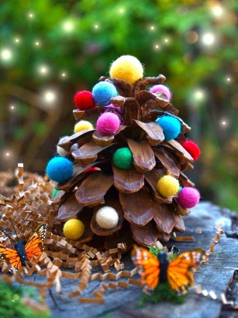 Чтобы лесная шишка заиграла яркими красками, в качестве декора используйте разноцветные шары из войлока