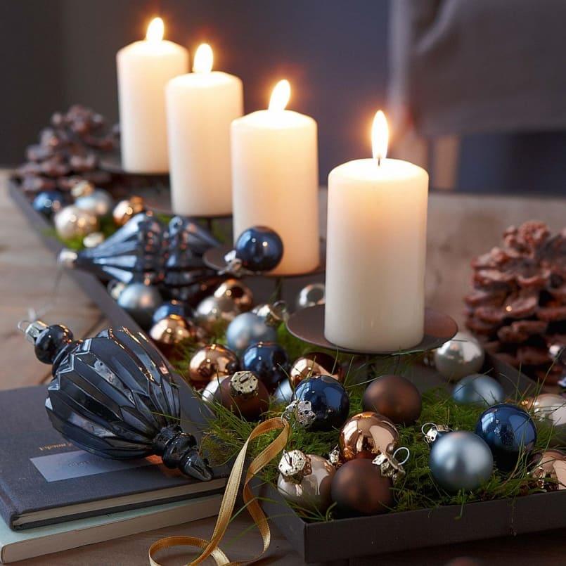 Ароматические свечи, украшенные ёлочными игрушками послужат хорошим дополнением новогоднего стола