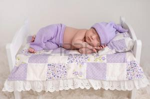 Nine day old newborn baby girl sleeping on a tiny white bed with pillow and patchwork quilt. She is wearing lilac colored pajamas with sleeping cap. Фото со стока