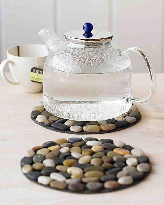 Приклеив гладкие камни к деревянному или резиновому основанию можно получить оригинальную подставку для чайника