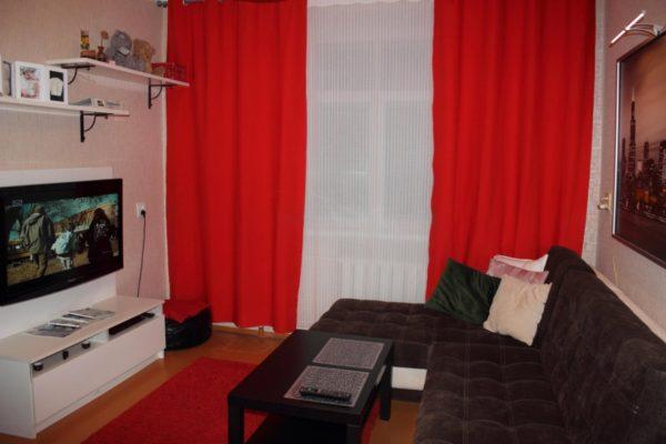 красные шторы с темным диваном