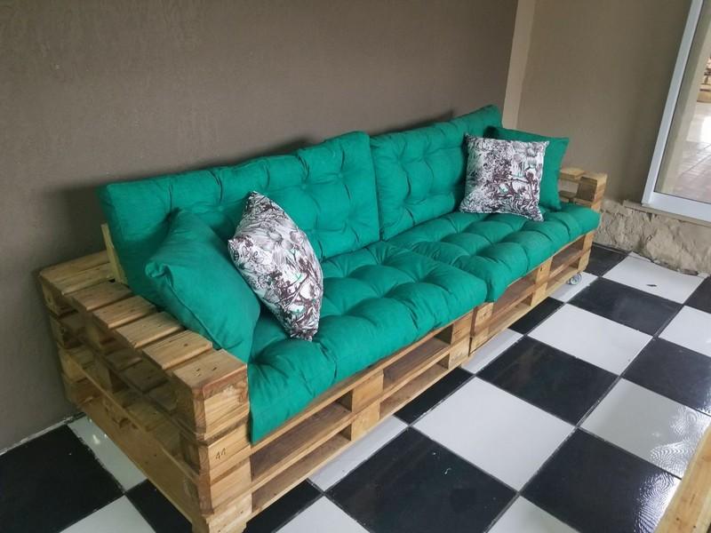 диван из деревянных поддонов зеленый матрас и пестрые подушки