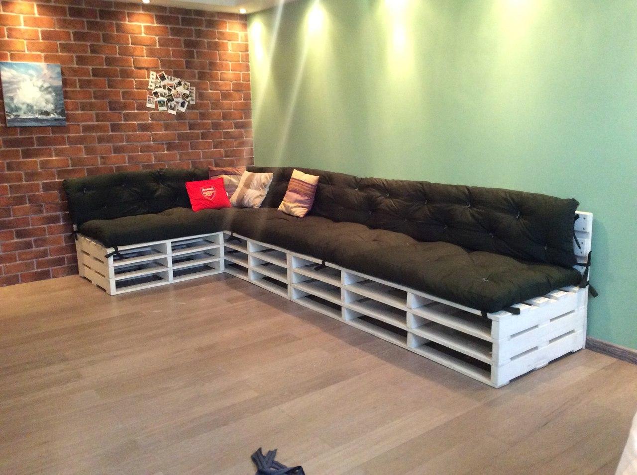 Угловой диван из поддонов черный матрас в комнате