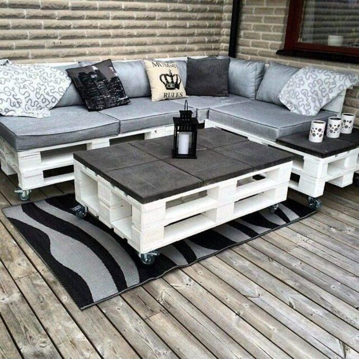 Угловой диван из поддонов серый матрас с подушками и столом в коттедже