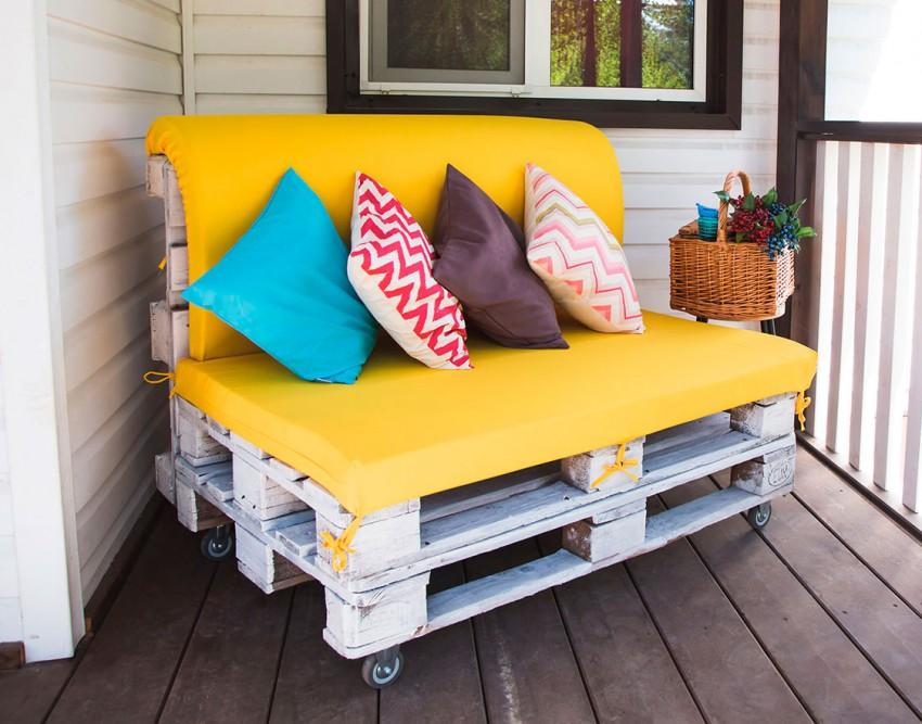 диван из деревянных поддонов желтый матрас и пестрые подушки